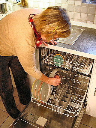 Female preparing a dishwasher for spring cleaning