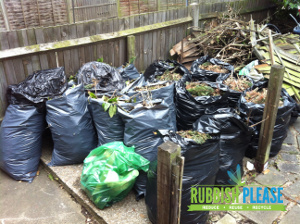 Black bags of green waste stored by the garden clearance team in London